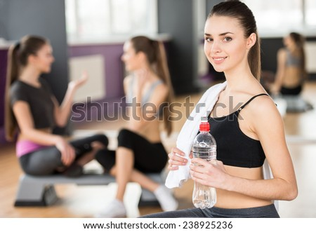 Sporty, beautiful young woman with water in the gym. Two other women in the background. - stock photo