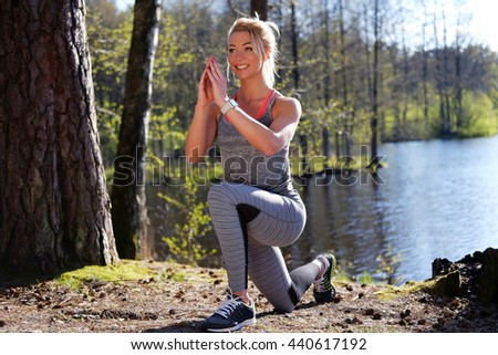 Sporty blond female doing fitness exercises near wild river in warm summer day.