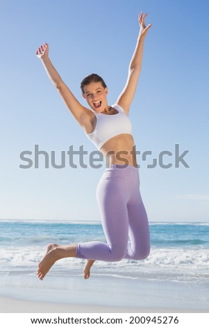 Sporty blonde jumping on the beach with arms out on a sunny day - stock photo