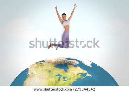 Sporty blonde jumping with arms out against blue sky - stock photo