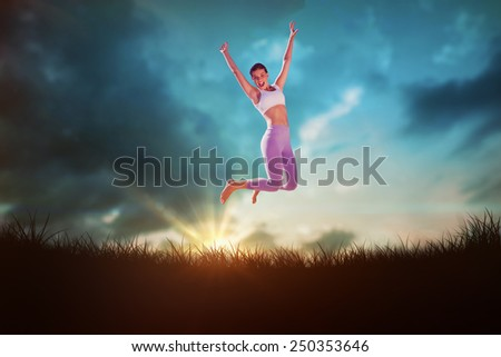 Sporty blonde jumping with arms out against blue sky over grass - stock photo