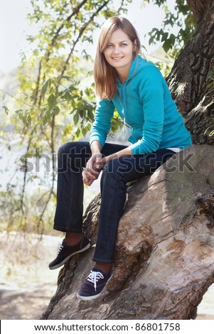 Sporty blue-eyed smiling woman sitting on a tree against blurred background with selective focus - stock photo