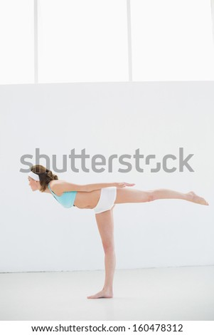 Sporty brunette woman stretching standing in a sports hall wearing sportswear