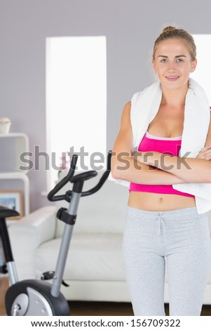 Sporty cheerful blonde standing cross armed in bright living room - stock photo