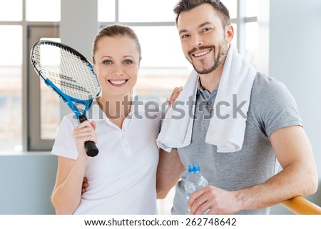 Sporty couple. Cheerful young sporty couple bonding to each other and smiling while both standing in sports club  - stock photo