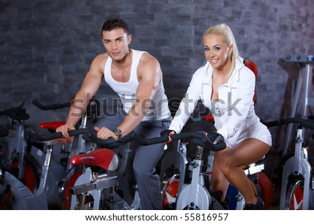 Sporty couple exercising at the gym - stock photo