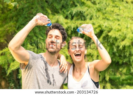 Sporty couple refreshing with cold water after run training in the park - Sport fitness young happy models taking a break after jogging in the nature - stock photo