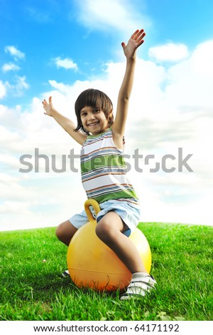 Sporty cute positive kid, playing happily with big ball on green meadow