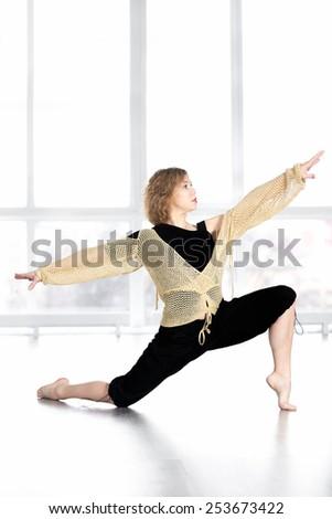 Sporty dancer woman in class dancing, doing aerobics training, fitness choreography zumba, balancing in lunge - stock photo