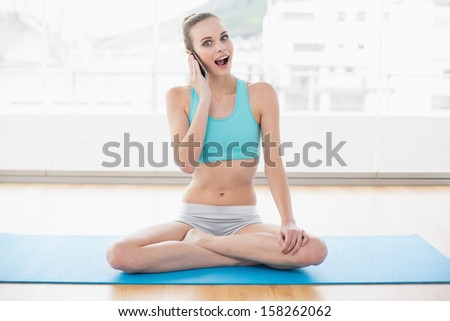 Sporty excited woman phoning in bright room