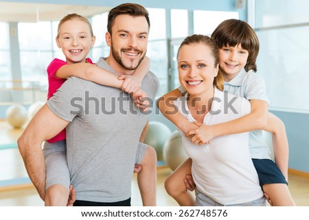 Sporty family. Happy sporty family bonding to each other while standing in sports club together   - stock photo