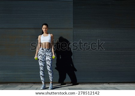 Sporty female taking break during her training with weights dumbbells, beautiful young woman in sporty clothing training bicep curls outdoors with copy space background for text message by side - stock photo