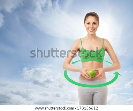 Sporty, fit and beautiful girl with the apple in the arrows cycle (healthy eating, vitamins and nutrition concept) - stock photo