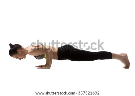 Sporty fit beautiful young brunette woman in sportswear bra and black pants working out, doing push-ups, chaturanga dandasana, four-limbed staff pose, studio full length, isolated, white background - stock photo