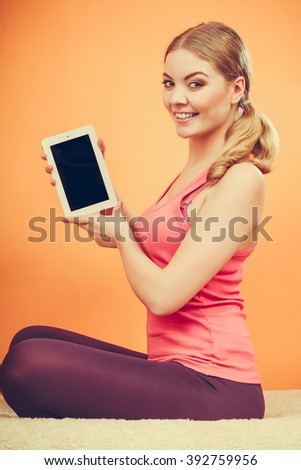 Sporty fitness girl holding tablet computer with blank screen showing copyspace. Happy smiling woman advertising new modern technology. - stock photo