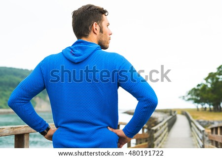 Sporty fitness man looking aside motivated for working out  outdoor. Sport strong male exercising outsides on a park in Rodiles, Asturias.