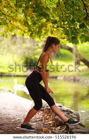 Sporty girl listens to music through headphones in autumn park
