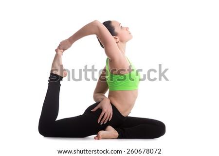 Sporty girl on white background doing back bend eka pada radjakapotasana (one-legged King Pigeon yoga Pose), asana for stretching neck, shoulders, chest, abdomen, groin, thighs - stock photo
