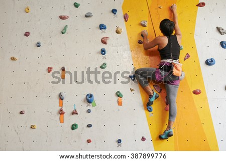 Sporty girl practicing climbing in the gym, rear view - stock photo