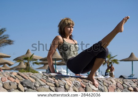 Sporty girl stretching on the beach - stock photo