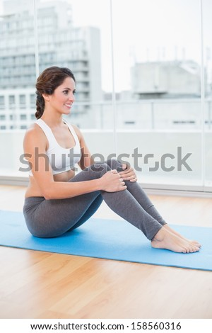 Sporty happy brunette sitting on exercise mat in bright room