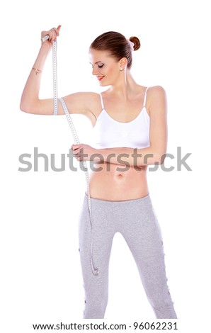 Sporty healthy woman on white background. She is measuring her arm with a  metric tape measure - stock photo