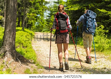 Sporty hikers on path with trekking poles - stock photo