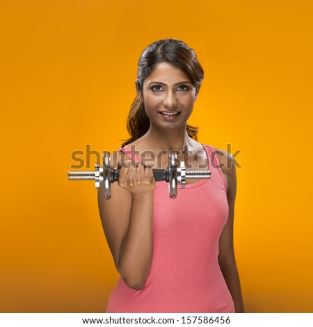 Sporty Indian woman exercising with dumb bell weights.  On a bright orange background.  - stock photo