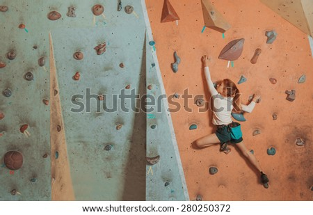 Sporty little girl climbing artificial boulder on practical wall in gym - stock photo