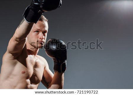 Sporty man during boxing exercise making direct hit