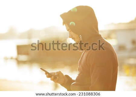 Sporty Man Holding Mobile Phone Outdoors - stock photo