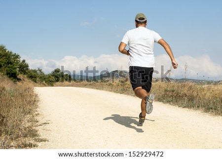 Sporty man running down the sandy track. - stock photo
