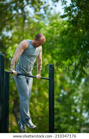 Sporty man training on special equipment outside - stock photo