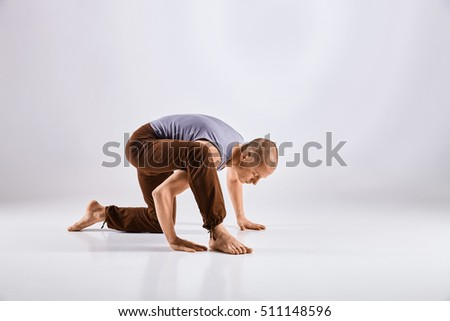 Sporty middle age man doing yoga practice isolated on white background - concept of healthy life and natural balance between physical and mental evolution