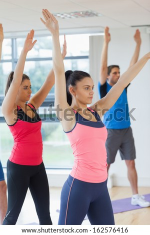 Sporty people doing power fitness exercise at yoga class in fitness studio - stock photo