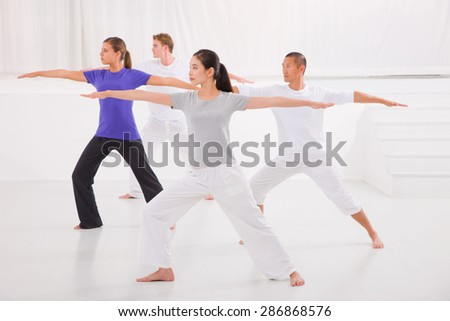 Sporty people stretching hands yoga class in fitness studio - stock photo