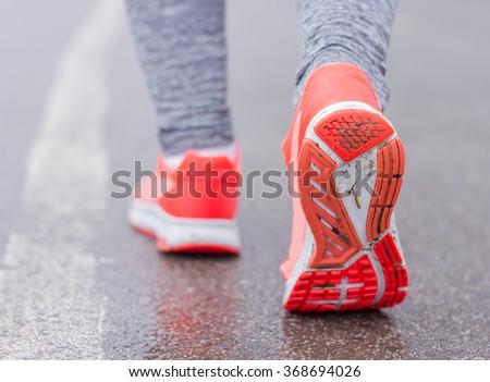 Sporty Runner feet running on the wet road. - stock photo