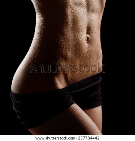 Sporty sexy girl with great abdominal muscles in black sportswear and drip drops of water on black background - stock photo