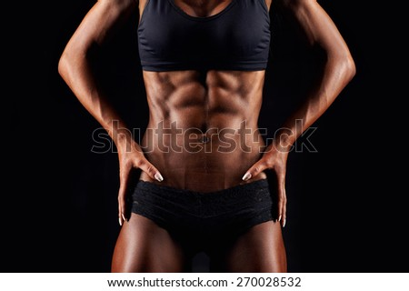 Sporty sexy girl with great abdominal muscles in black sportswear. Tanned young sexy athletic girl. A great sport female body close up. - stock photo