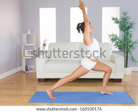 Sporty slim woman practicing yoga pose for stretching her body in her living room - stock photo