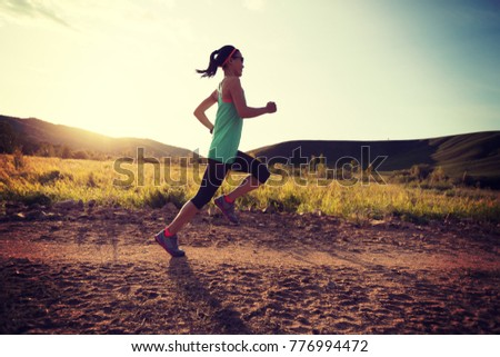 sporty trail runner woman running on sunset mountain