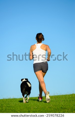 Sporty woman and dog running and training together outdoor at park on summer or spring. Female athlete exercising with her pet. - stock photo