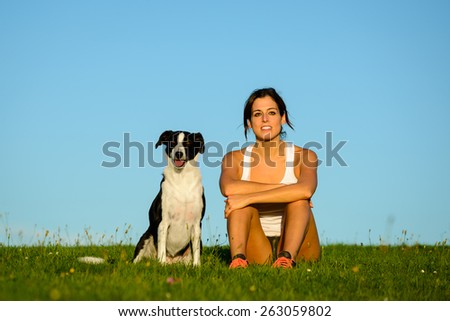 Sporty woman and dog sitting on grass field after running and exercising together. Female athlete with her pet taking a workout break for looking the sunset and relax. - stock photo