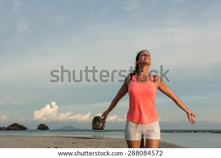 Sporty woman breathing enjoying relax and freedom at the beach, Krabi, Thailand. - stock photo