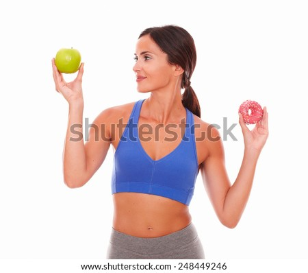 Sporty woman choosing healthy apple over sugary cake on isolated background