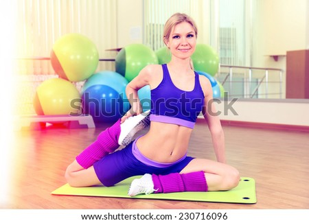 Sporty woman doing exercises in gym - stock photo
