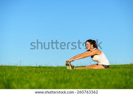 Sporty woman doing fitness stretching legs exercise. Brunette athlete on outdoor workout.