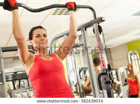 Sporty woman doing hard pull-up workout in health club. - stock photo