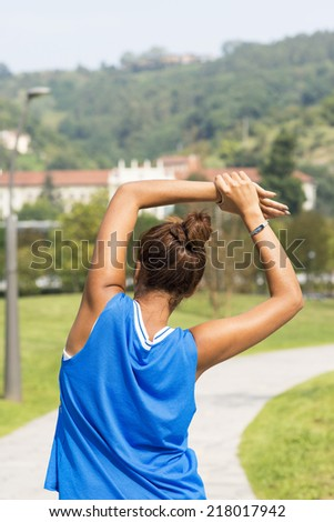 Sporty woman doing stretches before exercising in the park.