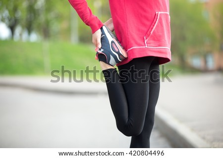 Sporty woman doing stretching exercises in park before training. Female athlete preparing for jogging outdoors. Runner getting ready for running routine. Sport active lifestyle concept. Close-up - stock photo